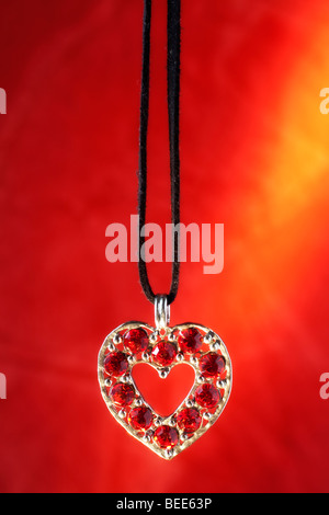 Heart shaped necklace with red stones and red  golden background