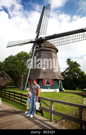 Father and daughter posing in front of a Dutch windmill. Edam, Holland - Stock Photo