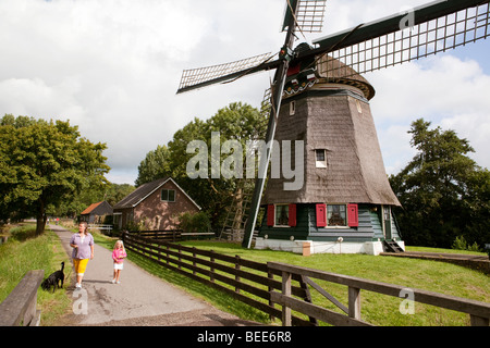 Mother and daughter walking the dog along a windmill. Edam, Holland - Stock Photo