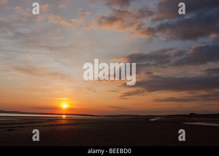 Wide angle view of sunset over the beach in Camber Sands, Sussex, England. - Stock Photo