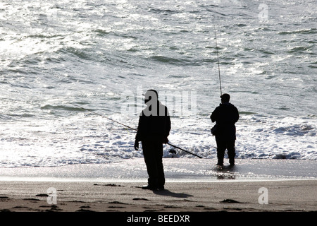 Local men fishing off the beach in Pacifica (Northern California near San Francisco) in the late afternoon - Stock Photo