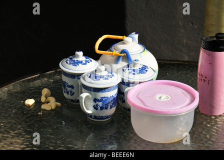 Cloves of garlic, a Chinese tea set and a pink thermos flask, Beijing, China - Stock Photo