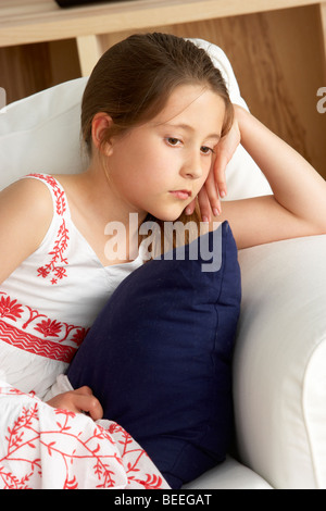 Young Girl Sat on Sofa at Home - Stock Photo
