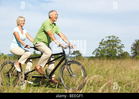 Mature couple riding tandem - Stock Photo