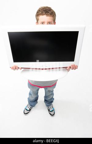 Portrait of Smiling Teenage Boy Holding Television - Stock Photo