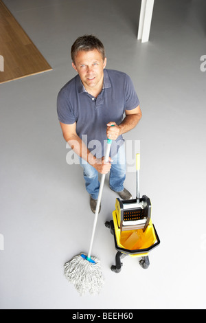Cleaner mopping office floor - Stock Photo