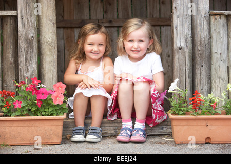Two Young Girls Playing in Wooden House - Stock Photo