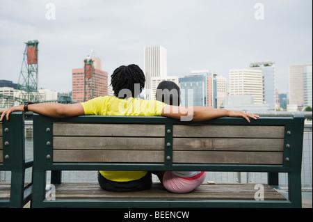 Couple sitting on bench overlooking cityscape Stock Photo