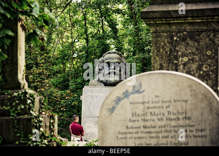 A man in maroon shirt stands in front of the grave of Karl Marx in Highgate Cemetery London England. - Stock Photo