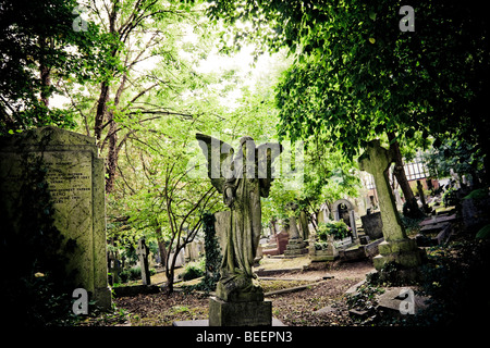 A Stone angel sculptured headstone stands over a grave amongst trees in Highgate Cemetery North London England UK - Stock Photo