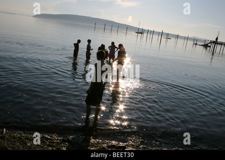 Kids on summer vacation wade into the water at sunset, Washington State, USA - Stock Photo
