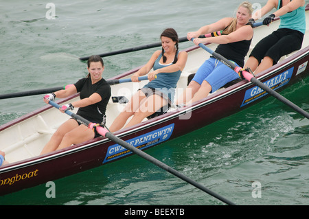 Four women rowing celtic longboat in a competitive race at Aberystwyth Wales UK - Stock Photo