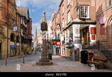 The Ancient Cross and The Rows Shopping Area on Bridge Street, Chester, Cheshire, England, UK - Stock Photo