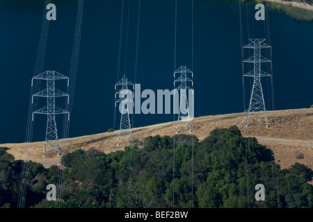 aerial view above power transmission lines towers at California reservoir - Stock Photo