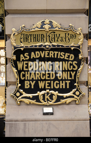 Sign advertising wedding rings charged by weight outside Arthur Kay and Bro jewellers shop in Manchester, England, - Stock Photo