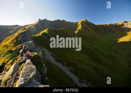 Early in the morning, a photographer gazing at the 'Val de Courre' (Auvergne). Photographe admirant le Val de Courre - Stock Photo
