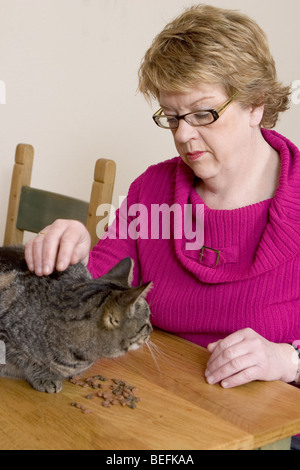 Mature woman stroking cat on the table - Stock Photo