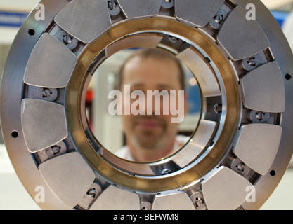 Worker is looking through a ball bearing - Stock Photo