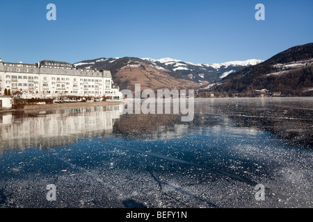 Zell am See Austria Europe. January Frozen Zeller See lake and lakeside Grand Hotel in alpine resort in winter - Stock Photo