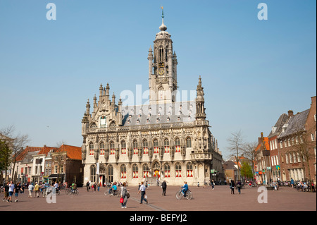 Passers-by on the market square in front of the late-Gothic town hall of Middelburg. - Stock Photo