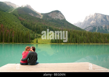 young couple sitting on dock - Stock Photo