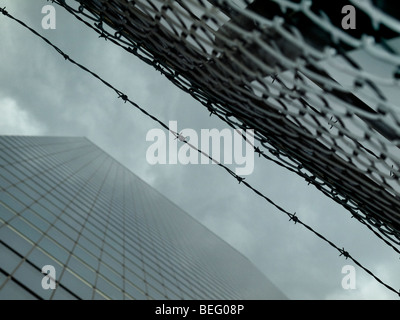 High modern skyscraper on a background of a cloudy sky with a fence and a barbwire. - Stock Photo