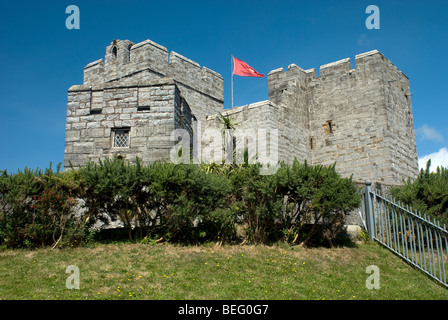 Detail of part of the castle showing the battlements and a red IOM flag in Castletown, Isle of Man on a sunny day - Stock Photo