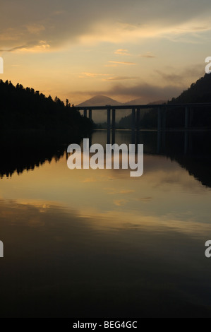 View of Jezero Bajer lake in Fužine (Gorski kotar, Croatia, Europe) and higway bridge in sunset with mountains in - Stock Photo