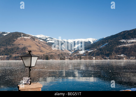 Zell am See Austria Europe. Scenic view from Stadtpark across frozen Zeller See lake and snow-capped alpine mountains - Stock Photo
