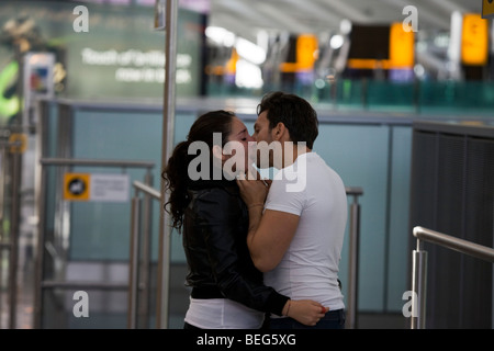 Departing lovers say their emotional farewells in Departures at Heathrow Airport's Terminal 5. - Stock Photo