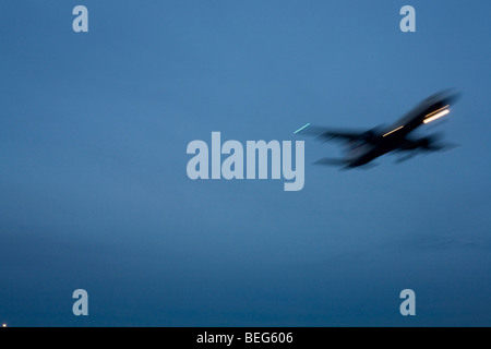 Last (4th) of a sequence of 4 consecutive images, a blurred jet airliner passes overhead, nearing its final airport - Stock Photo