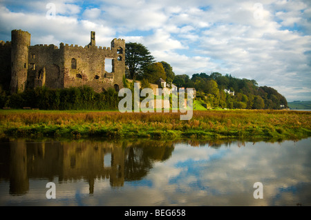 Laugharne castle in West wales With Dylan Thomas' Boathouse in the distance - Stock Photo