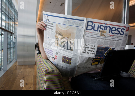 In the British Airways Galleries First lounge at Heathrow Airport's T5 a passenger reads the Business section of - Stock Photo