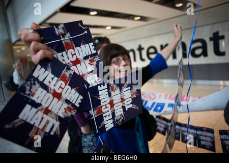 A mother awaitng her son in Arrivals of Heathrow's terminal 5 excitedly waves a Welcome Home Matt banner - Stock Photo