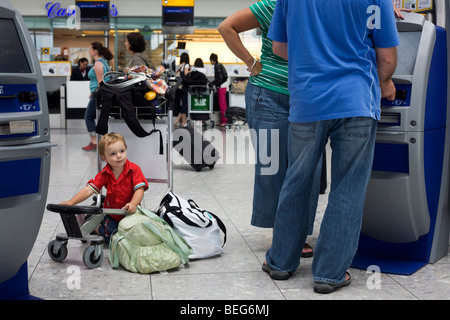 A scene of busy modern air travel as international passengers check-in at the British Airways Heathrow Airport's - Stock Photo