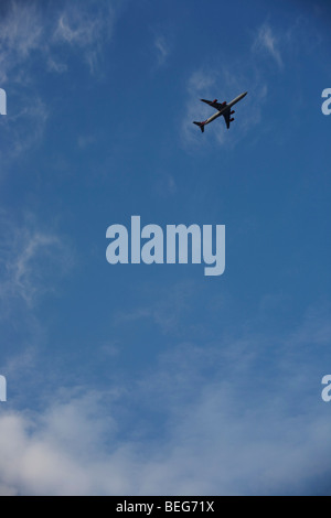 In the top-right corner of the image, an airliner passes overhead in the clear blue sky flight-path over South London - Stock Photo
