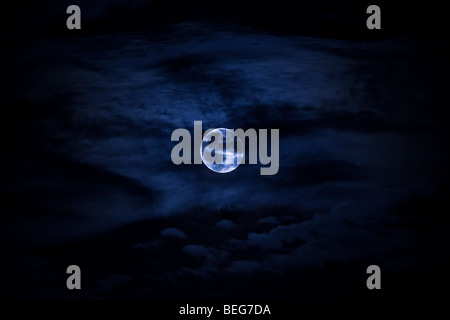 Full moon behind clouds cold blue color - Stock Photo