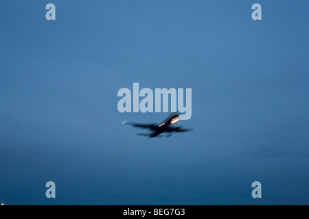 Third of a sequence of 4 consecutive images, a blurred jet airliner passes overhead, nearing its final airport descent. - Stock Photo