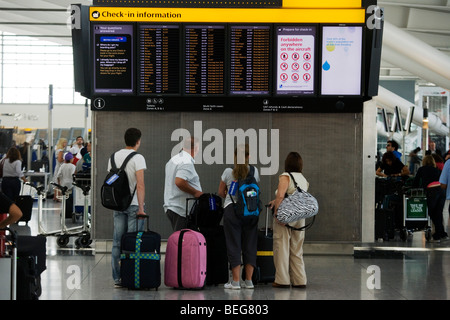 Passengers read flight departure information in the departures concourse at Heathrow's Terminal 5. - Stock Photo