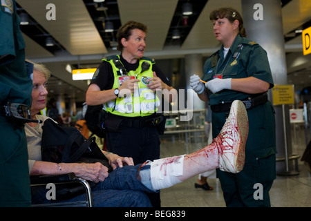 NHS Paramedic Responders attends a lady passenger in Heathrow's terminal 3 who has tripped and badly gashed her - Stock Photo