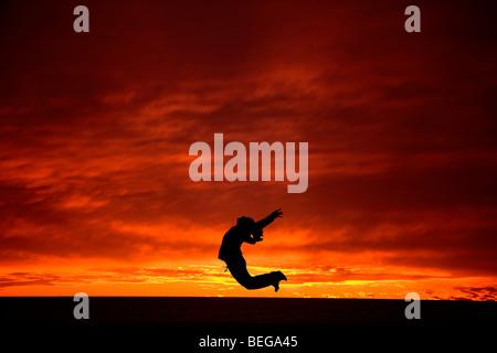 Jumping for Joy at dawn or dusk. - Stock Photo