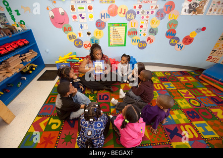 Detroit, Michigan - A teacher tells a story to children at the World of Wonders Child Care Center. - Stock Photo