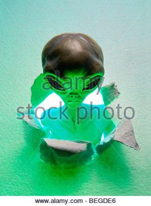 A green alien bursting through paper. - Stock Photo