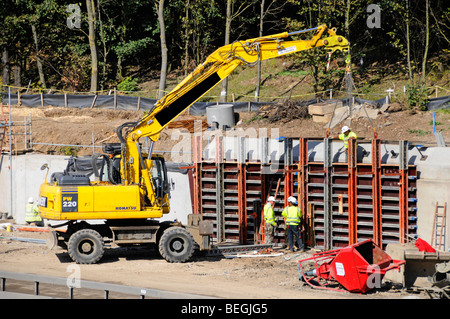 Workmen working on concrete  retaining wall structure as part of M25 motorway road widening scheme - Stock Photo
