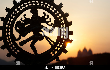 Dancing lord Shiva statue, Nataraja silhouette, against an indian temple sunrise background. Puttaparthi, Andhra - Stock Photo