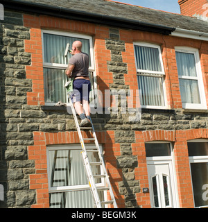 Self employed man sole trader standing on ladder cleaning windows of a terraced house, Aberystwyth Wales UK - Stock Photo