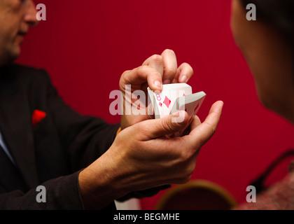 A close up magician doing card tricks at a wedding reception party, UK - Stock Photo