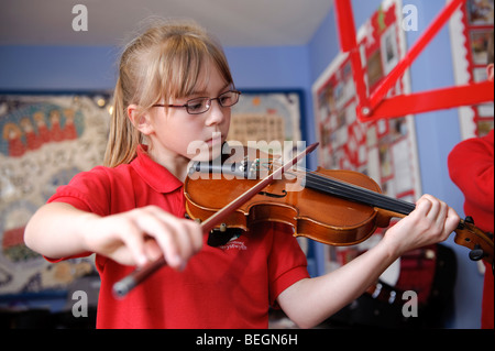 a Young girl primary school pupil learning to play the violin in school, Wales UK - Stock Photo