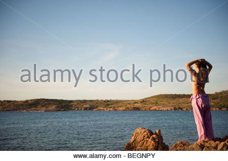 Attractive relaxing on the beach with a sea view at sunset time in Sardinia, Italy - Stock Photo