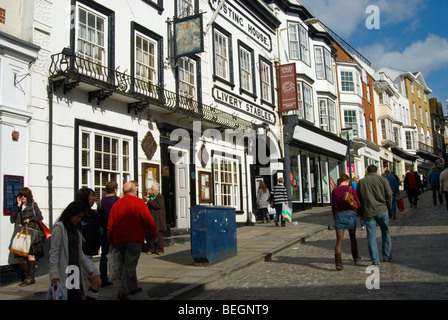Old Livery stables on Guildford High Street with shoppers walking in the sunshine - Stock Photo